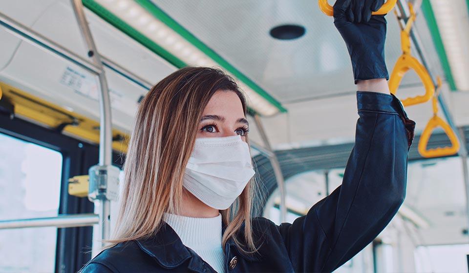 Vrouw met mondmasker op in het OV